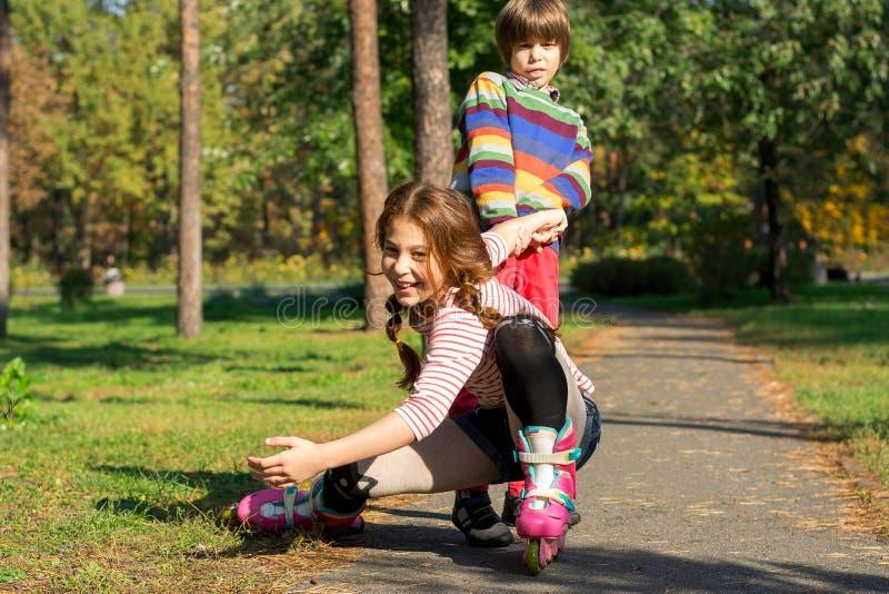 一个小男孩培养在溜冰鞋跌倒的他的姐妹 免版税图库摄影