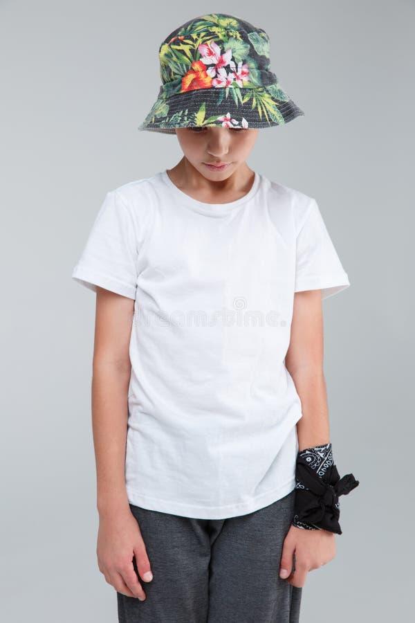 一个小男孩正确地站立,并且看得下来 在一个灰色背景 免版税库存图片