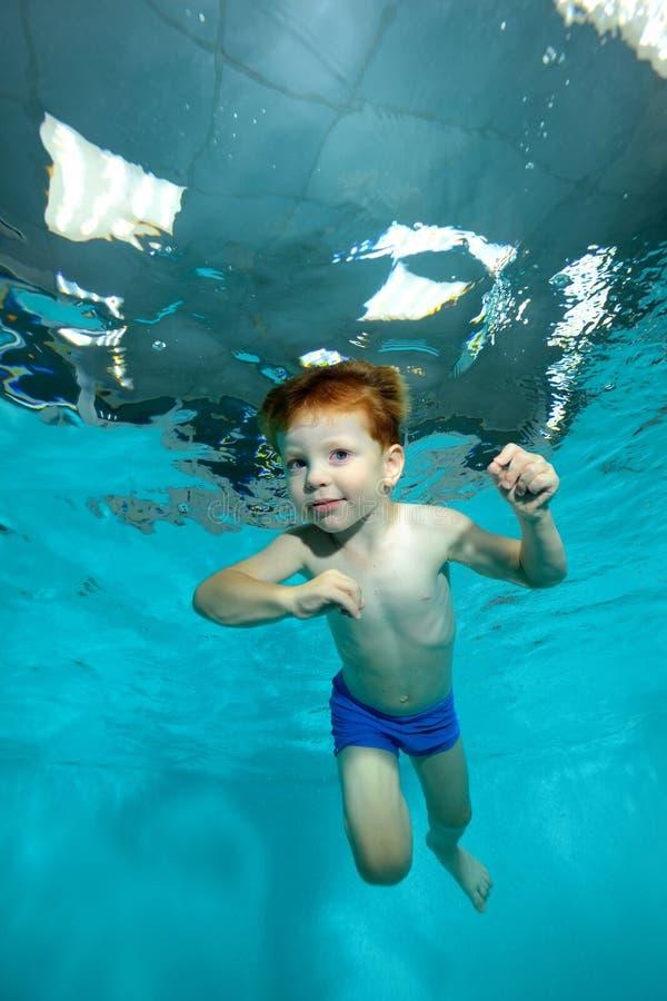 一个小男孩漂浮在水池的水下在蓝色背景 免版税库存照片