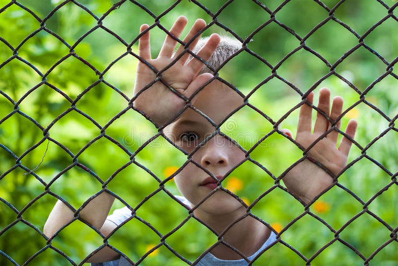 一个小男孩的抽象图片在链节篱芭后的 照片 免版税图库摄影