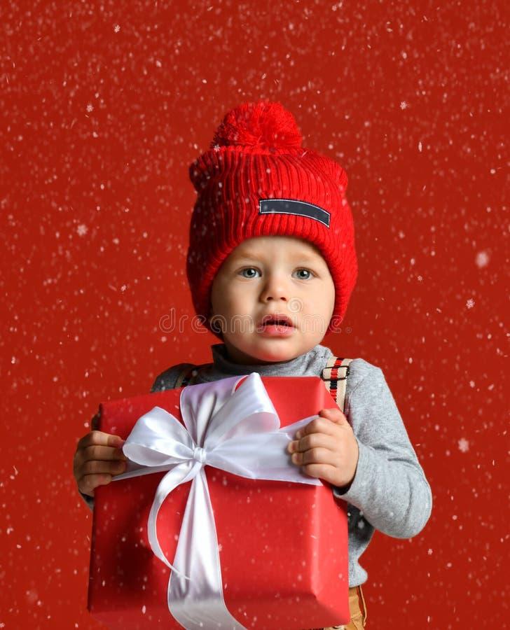 一个小男孩的画象一个红色帽子的有绒球的 拿着有一把白色弓的一个大礼物盒 免版税库存图片