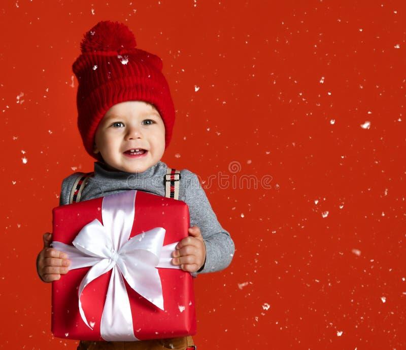 一个小男孩的画象一个红色帽子的有绒球的 拿着有一把白色弓的一个大礼物盒 免版税库存照片