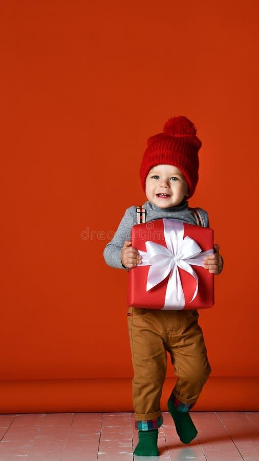 一个小男孩的画象有绒球的 拿着有一把白色弓的一个大礼物盒 图库摄影