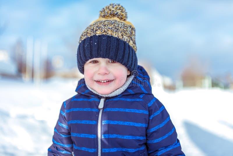 一个小男孩的画象3岁 特写镜头在新鲜空气的冬天 愉快的微笑的室外休闲 在蓝色 免版税库存照片