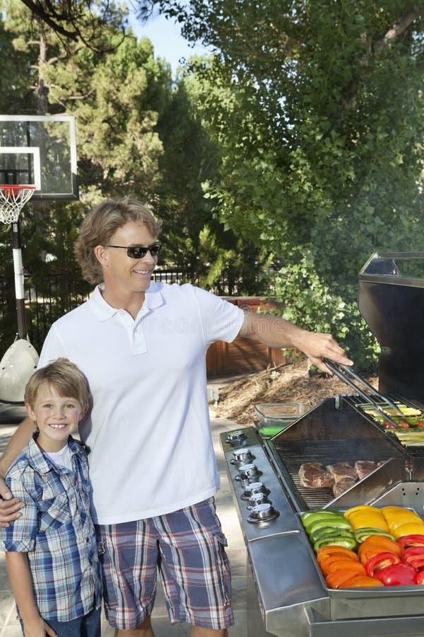 一个小男孩的画象有父亲烤的菜的在烤肉格栅在草坪 免版税库存图片