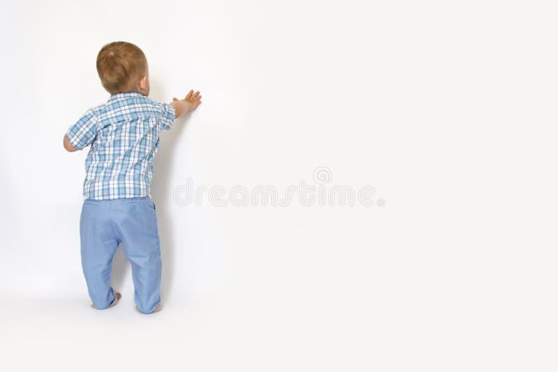 一个小男孩站立对墙壁 免版税库存图片