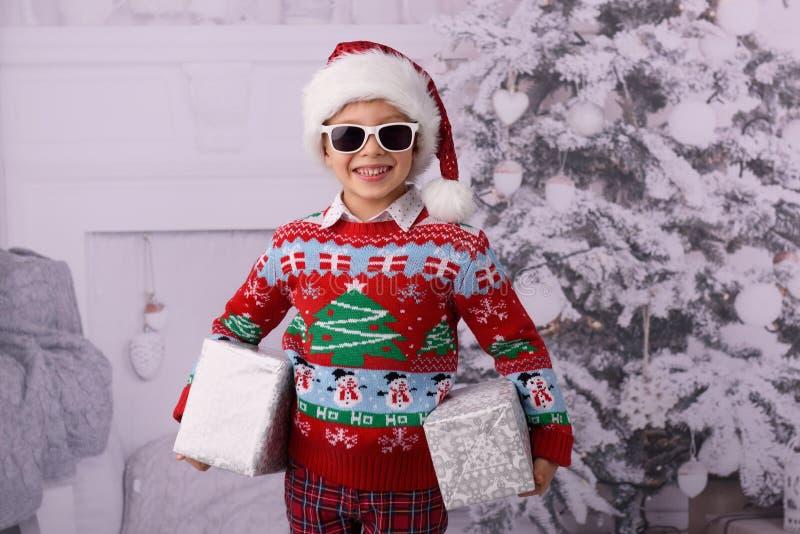 一个小男孩,微笑,看照相机,穿一件红色毛线衣 免版税库存照片