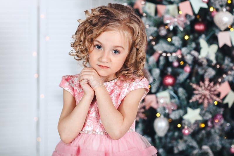 一个小白肤金发的女孩的画象有卷毛的在与明亮地色的灯笼和旗子的一棵树附近 库存图片