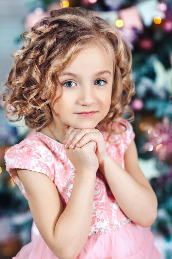 一个小白肤金发的女孩的画象有卷毛的在圣诞树附近 免版税库存图片