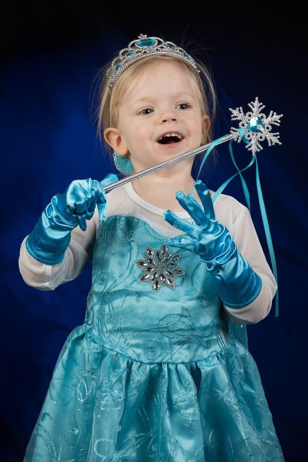 一个小白肤金发的愉快的女孩,打扮作为迪斯尼结冰的公主埃尔莎 图库摄影