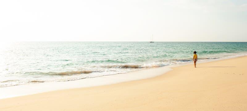 一个小的亚洲女孩身分,当放松在日落海滩时 免版税库存图片