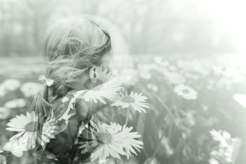 一个小的白肤金发的女孩和春天草甸的两次曝光图象 库存照片