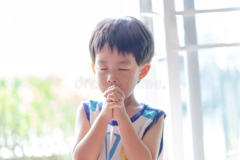 一个小的祷告,男孩祈祷严重和有希望地给耶稣 图库摄影