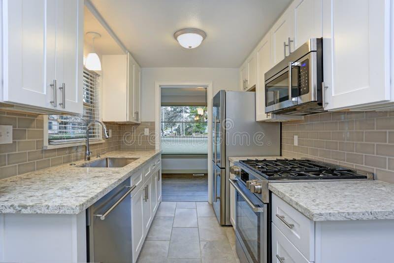 一个小紧凑厨房的照片有白色振动器内阁的 库存图片