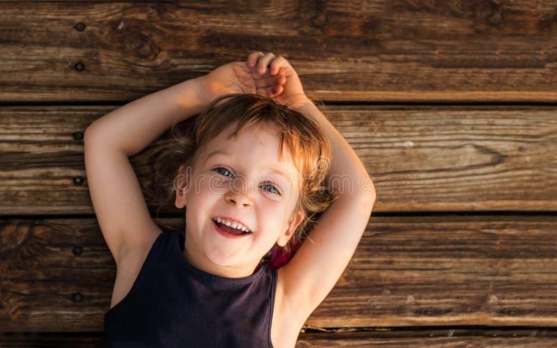 一个小红发女孩的画象,说谎在木地板上 图库摄影