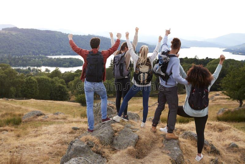 一个小组五个年轻成人朋友在山远足以后庆祝到达山顶,后面看法 库存照片