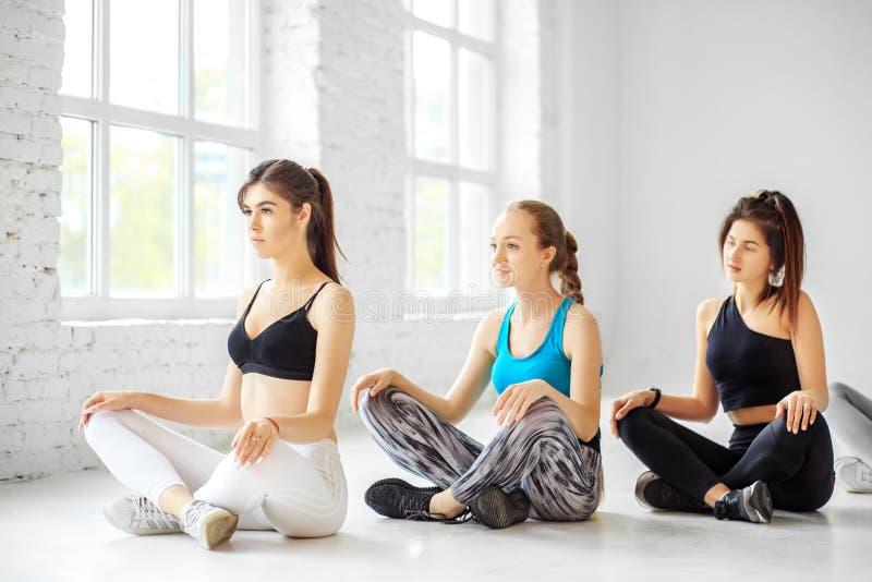 一个小组从瑜伽的妇女参与在健身房的训练 体育的概念,健康生活方式,健身,舒展 免版税图库摄影