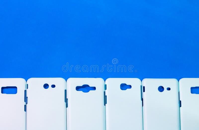 一个小组在生动的蓝色背景的电话盒 流动论点或智能手机保护者您的设计的 库存照片