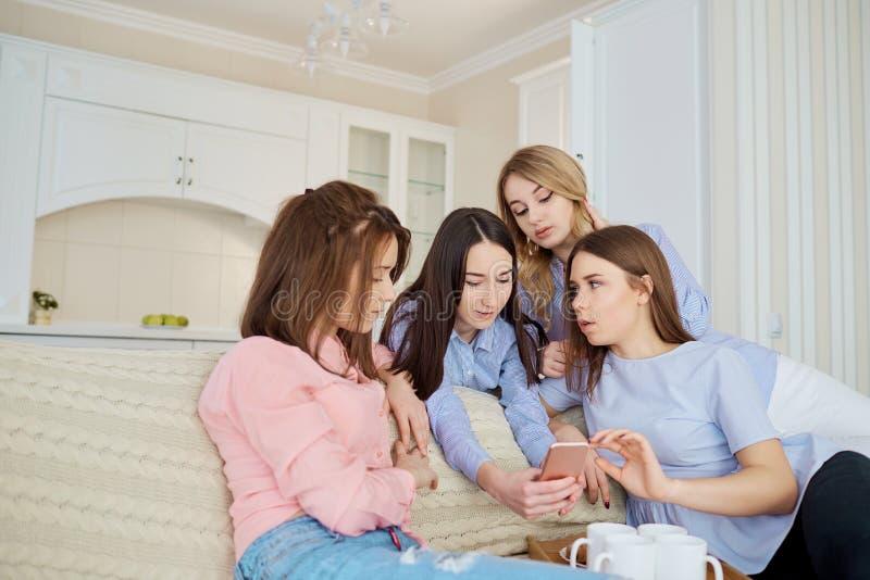 一个小组女孩`朋友看电话我 库存照片