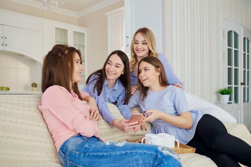 一个小组女孩`朋友看电话我 免版税库存图片