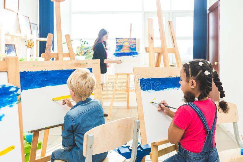 一个小组学龄前学生和年轻老师图画班油漆的在树胶水彩画颜料 混合的族种女小学生美国黑人 库存图片