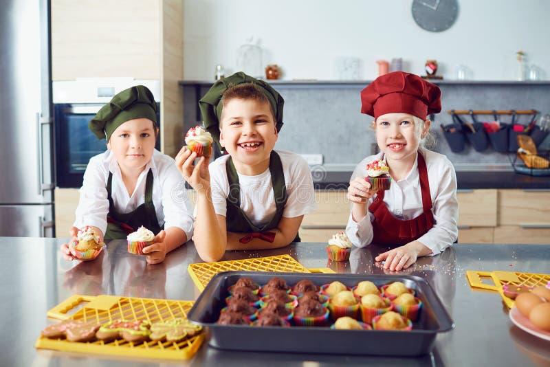 一个小组孩子在厨房里烹调 免版税库存图片