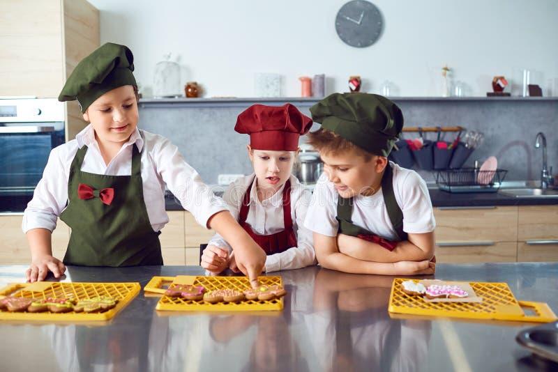 一个小组孩子在厨房里烹调 库存照片