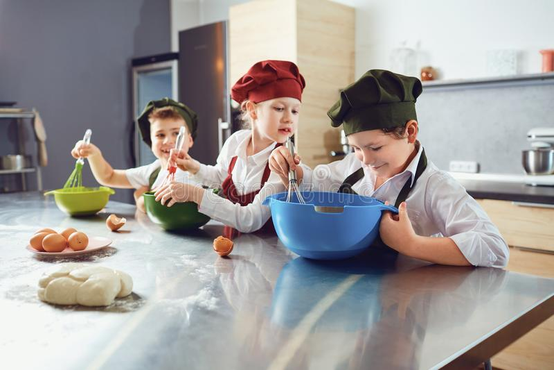 一个小组孩子烹调在桌上在厨房里 库存照片