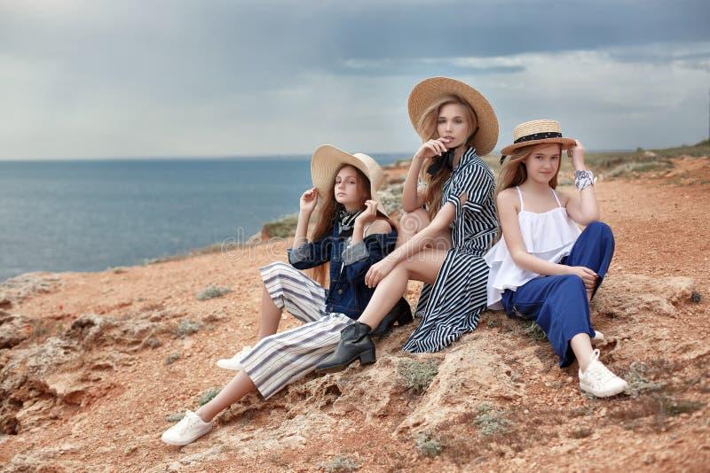 一个小组少女,蓝色海洋的岩石岸的少年 库存图片