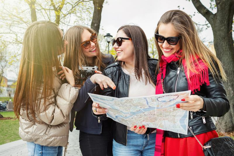 一个小组年轻女性游人在地图的欧洲城市寻找吸引力 四快乐和美丽 库存图片