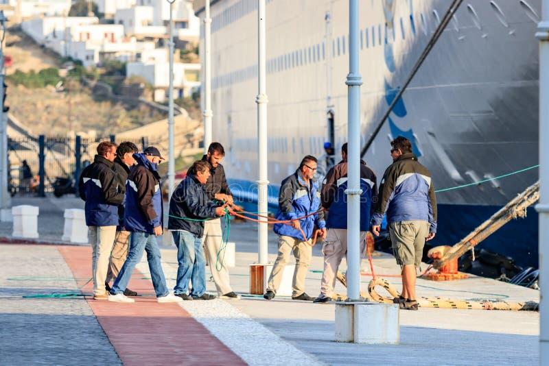 一个小组拉扯游轮的系泊缆的码头工人,靠码头在米科诺斯岛,希腊 库存图片