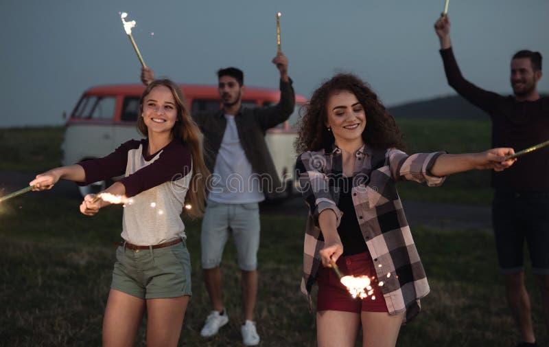 一个小组有站立户外在黄昏的闪烁发光物的朋友 免版税库存照片