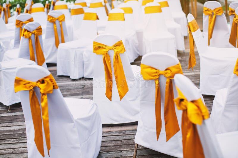 一个小组有金透明硬沙框格的白色氨纶椅子盖子海滩婚礼地点安排的 图库摄影