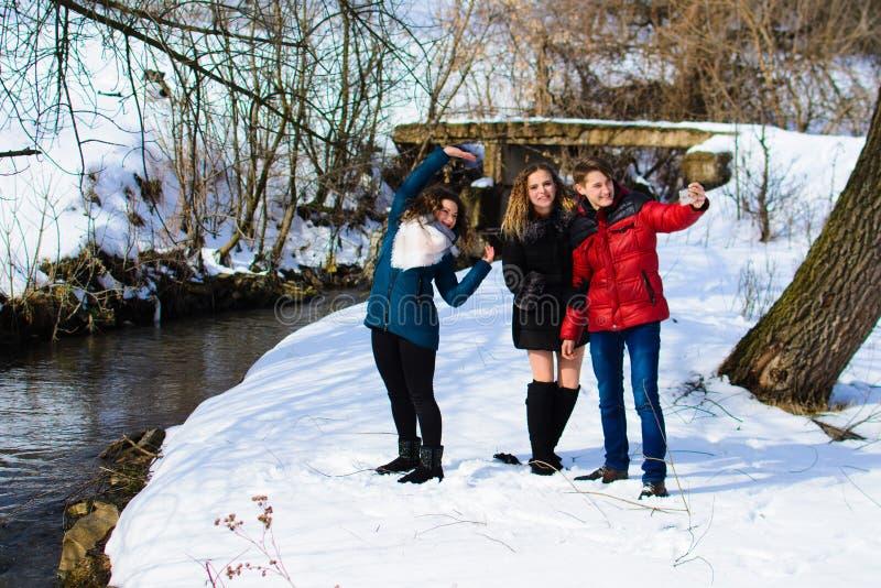 一个小组朋友在河附近做selfie在冬天 免版税库存照片