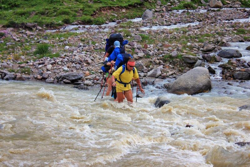 一个小组游人通过涉过的一条粗砺的山河 免版税库存图片