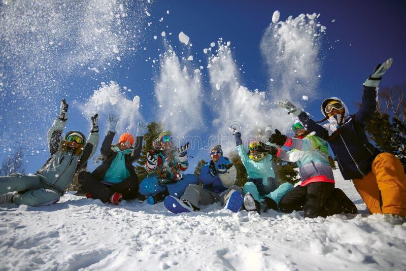 一个小组滑雪者和挡雪板乐趣投掷的雪的朋友 免版税库存照片