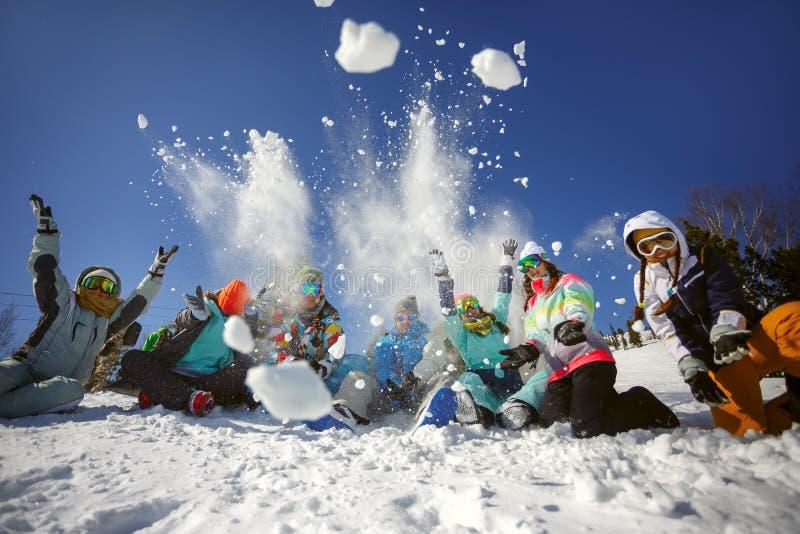 一个小组滑雪者和挡雪板乐趣投掷的雪的朋友 库存图片