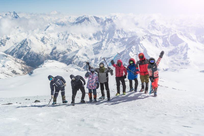 一个小组登山人是愉快和摇他们的在山的手 免版税库存照片