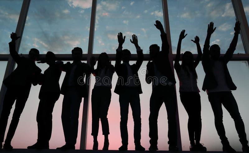 一个小组的剪影举他们的手的商人 图库摄影