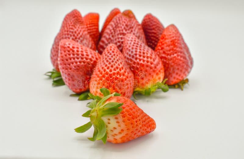 一个小组的接近的uo视图几个鲜美新鲜的红色草莓收获了并且准备被吃 草莓被投入 免版税图库摄影