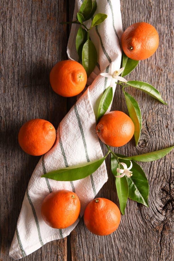 一个小组的特写镜头与一块毛巾和叶子的6个橘栾果在一张土气木桌上 免版税库存图片