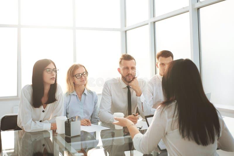一个小组的背景影像坐在书桌的商人 免版税库存图片