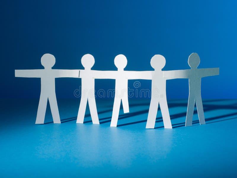 一个小组纸人剪影一起站立 他们中的一个是残疾 免版税库存照片