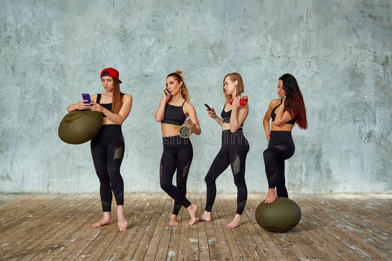一个小组美丽的健身女孩在灰色墙壁附近的健身屋子有的训练的情感地谈话的支柱, 免版税库存图片