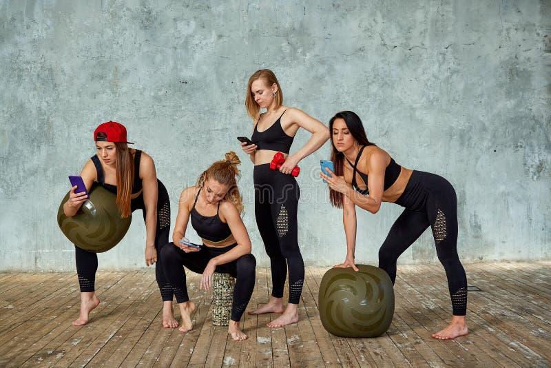 一个小组美丽的健身女孩在灰色墙壁附近的健身屋子有的训练的情感地谈话的支柱, 库存照片