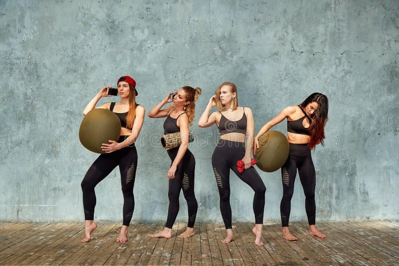 一个小组美丽的健身女孩在灰色墙壁附近的健身屋子有的训练的情感地谈话的支柱, 免版税图库摄影