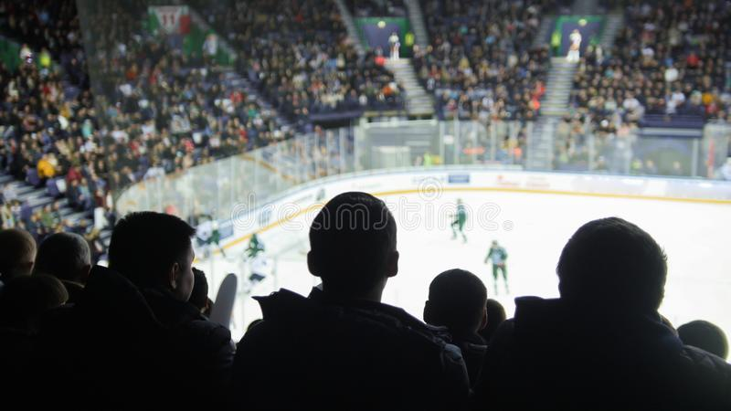 一个小组观看曲棍球比赛的年轻人剪影在一个闭合的体育场内 库存照片