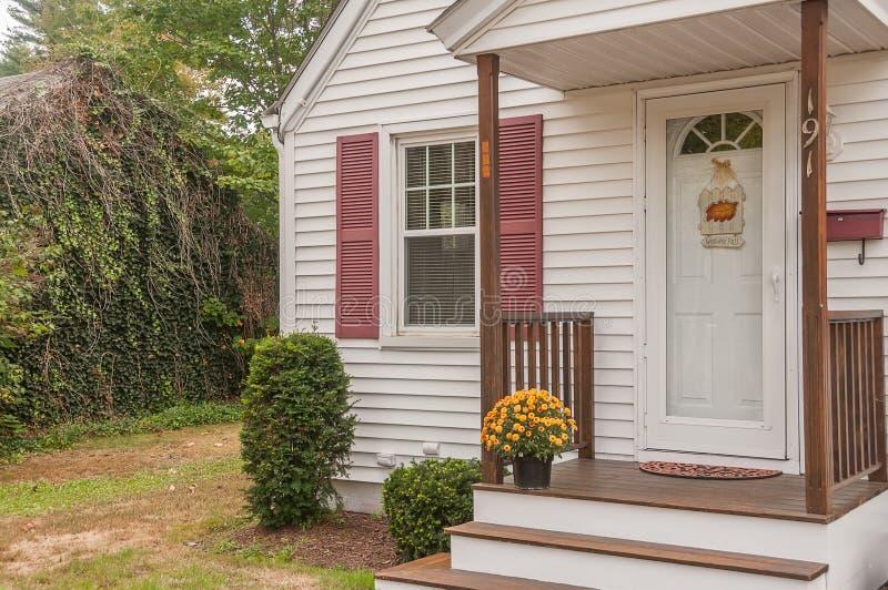 一个小舒适木房子的门廊和与在门限的黄色菊花 美国 缅因 家庭简单的舒适 免版税图库摄影