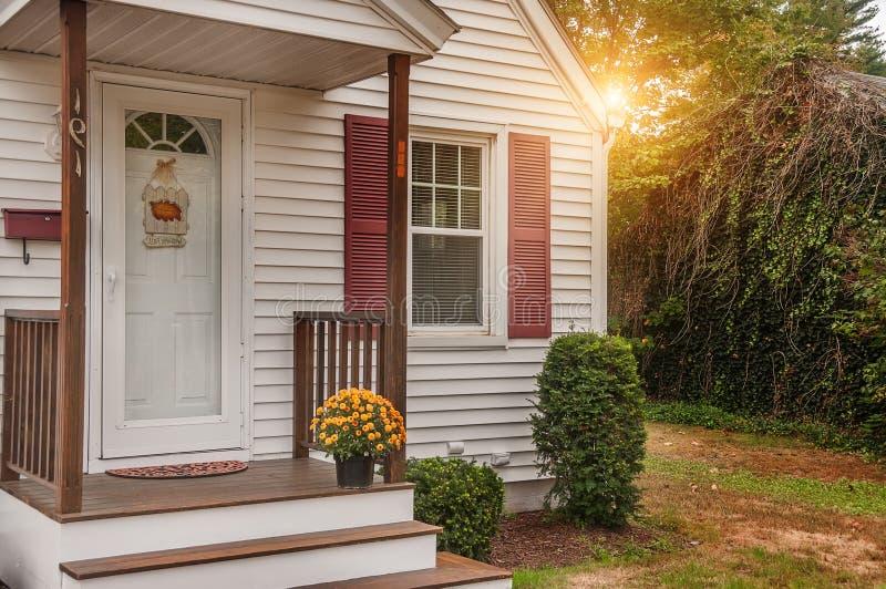 一个小舒适木房子的门廊和与在门限的黄色菊花 美国 缅因 家庭简单的舒适 库存图片