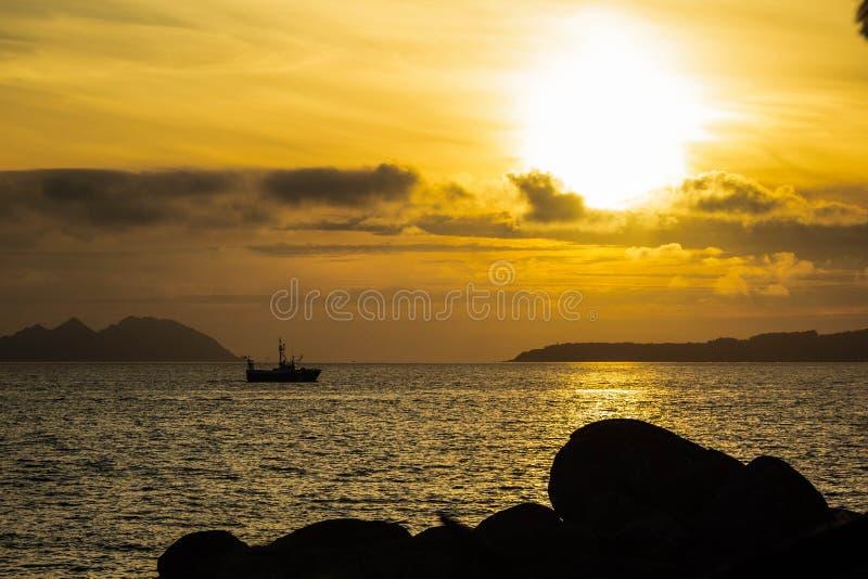 一个小船航行通过在日落期间的镇静水 免版税库存照片